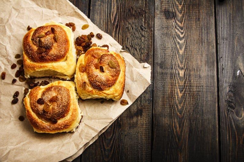 Petits pains fraîchement cuits au four avec de la cannelle avec des épices et des raisins secs sur le papier parcheminé Vue de ci photographie stock libre de droits