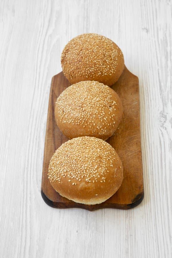 Petits pains frais d'hamburger avec le panneau en bois de seedson de sésame au-dessus du fond en bois blanc, vue courbe image libre de droits