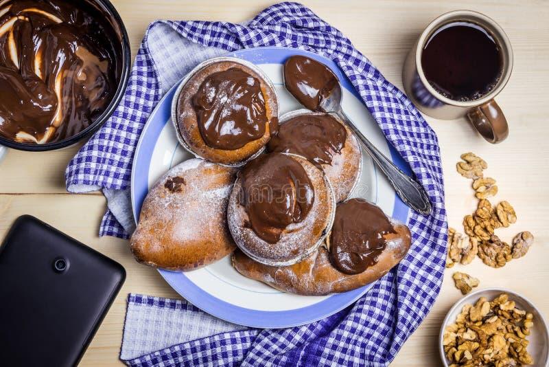 Petits pains frais de chocolat, crème au chocolat, thé noir et noix PC de tablette images libres de droits