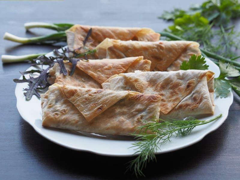 Petits pains frits appétissants avec des verts sur une table en bois foncée photo stock