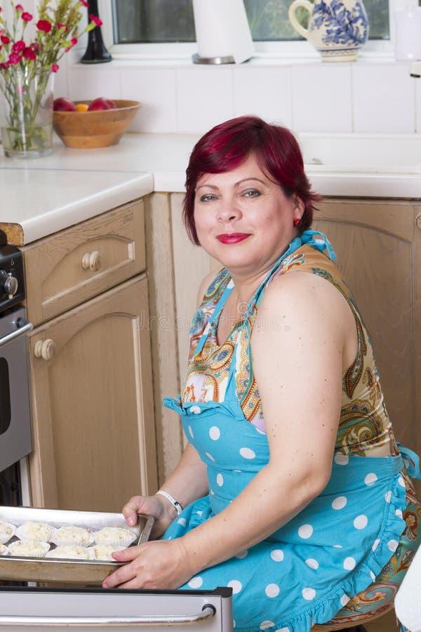 Petits pains mûrs de cuisson de femme à la maison photo libre de droits