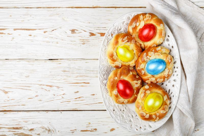 Petits pains traditionnels de P?ques d?cor?s des oeufs, des p?tales d'amande et du pain de f?te doux de zeste de citron sous form image libre de droits