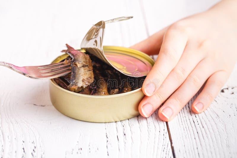 Petits poissons fumés dans tincan sur la table avec la fourchette photos stock