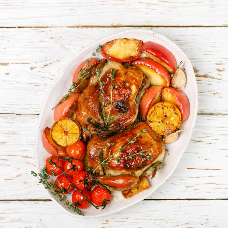 Petits poulets entiers cuits au four avec les pommes, le citron, l'ail, le thym, les tomates et les épices Photo carrée images stock