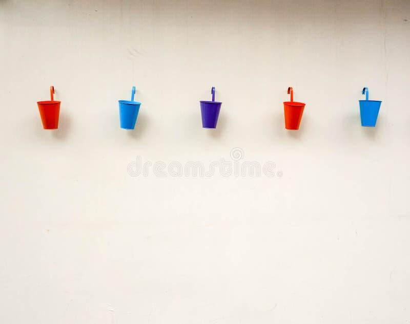 Petits seaux de couleur sur le fond de mur images libres de droits