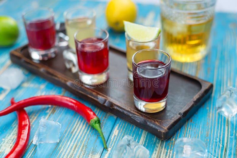 Petits verres avec les boissons colorées sur un conseil en bois images libres de droits
