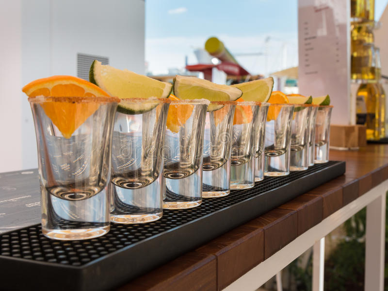 Petits verres en conformité avec des tranches d'orange et de chaux prêtes à Tequ images libres de droits