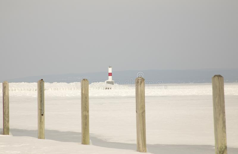 Petoskey Pierhead Lighthouse, Petoskey, Michigan in winter. Ice covered Petoskey Lighthouse in Petoskey Marina, Petoskey, Michigan on frozen Lake Michigan in stock images