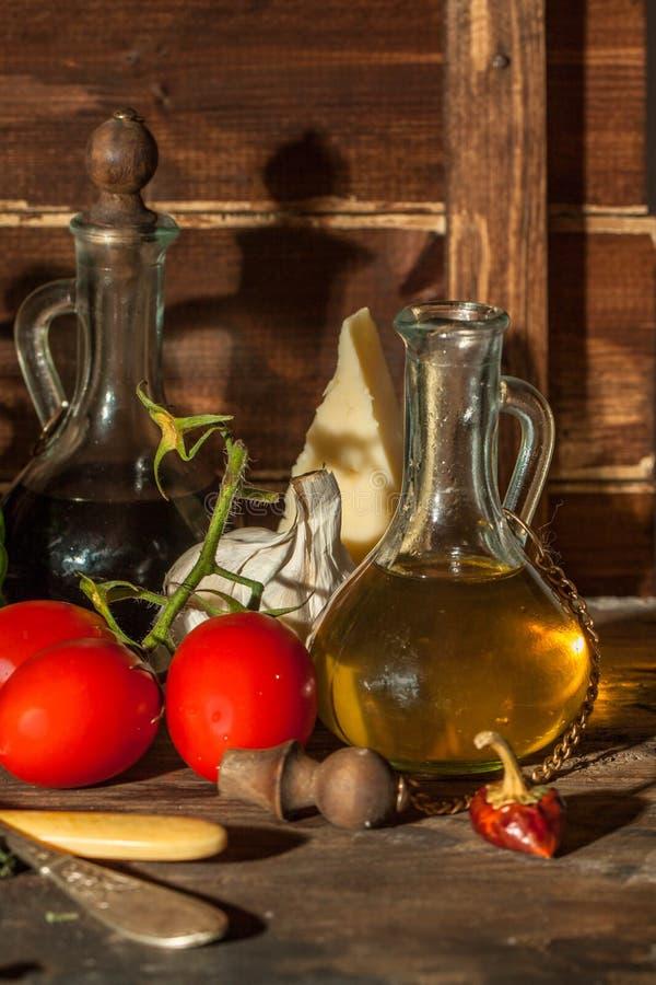 Petróleo, ajo, tomates y queso imagen de archivo