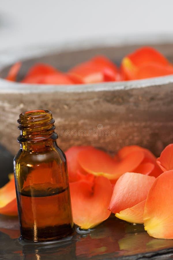 Petróleo de rosas de los productos del cuidado de la salud con un tazón de fuente imagen de archivo libre de regalías