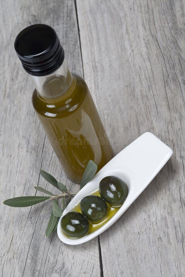 Petróleo verde-oliva e azeitonas em uma superfície de madeira imagem de stock royalty free