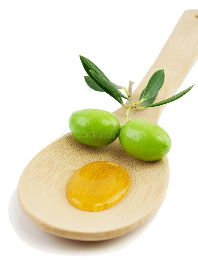 Petróleo verde-oliva e azeitonas frescas em uma colher de madeira imagem de stock