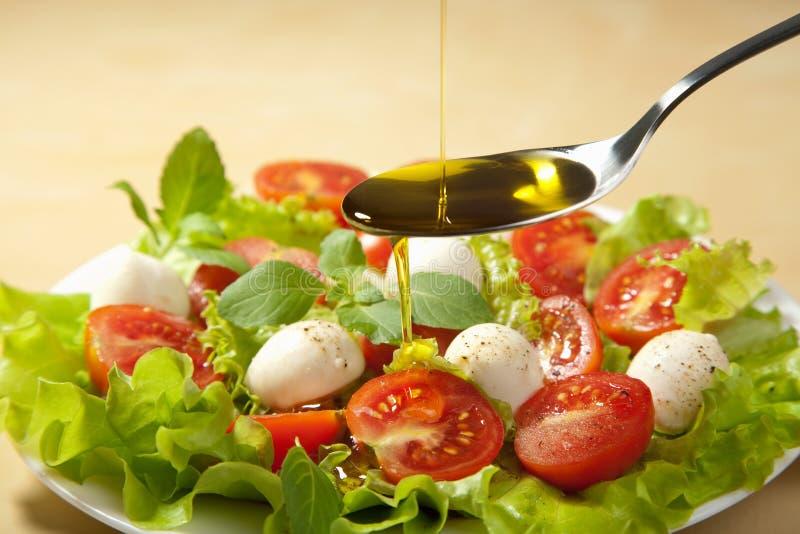 Petróleo verde-oliva que derrama sobre a salada fotos de stock