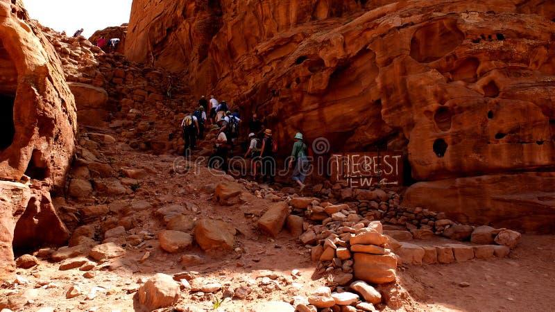Petra, Jordania 19 04 2014: Los turistas que emigran encima de la montaña con la mejor visión firman adentro el worldwonder en el foto de archivo