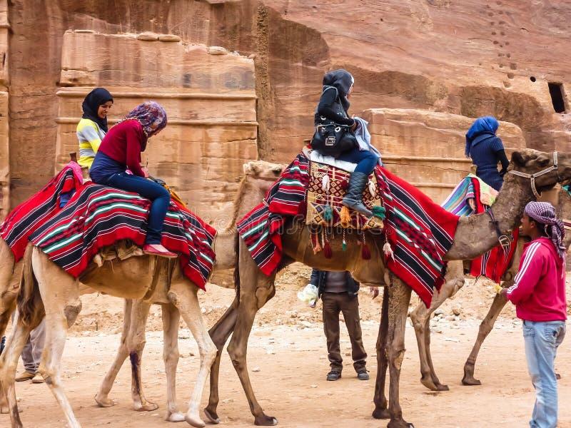 PETRA JORDANIEN: Grupp av turister på kamel i Petra Rose City arkivbilder