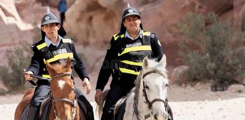 PETRA, Wadi Musa, Giordania, il 9 marzo 2018: Due poliziotti a cavallo con i cappucci divertenti del brufolo e le maglie del segn immagini stock