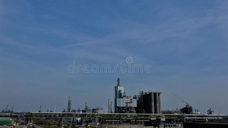 Petrochemical industrial complex under a blue sky at noon. Petrochemical industrial complex under a blue sky at high noon. Taken somewhere out west in the stock image