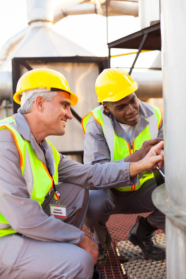 Petrochemical technicians inspecting. Two petrochemical technicians inspecting fuel tank in plant stock photos