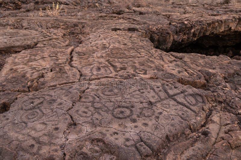 Petroglifos tallados en roca volcánica en Trail de rey, Kona, Hawaii imagen de archivo libre de regalías