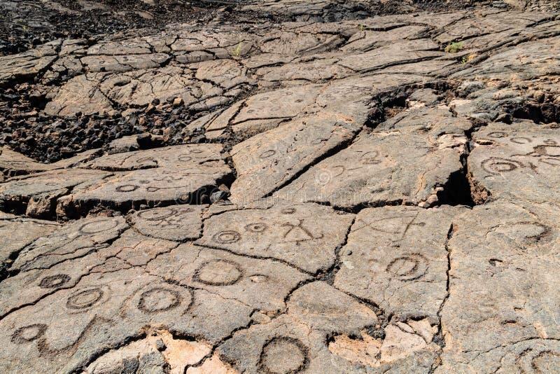 Petroglifos tallados en roca volcánica en Trail de rey, Kona, Hawaii foto de archivo