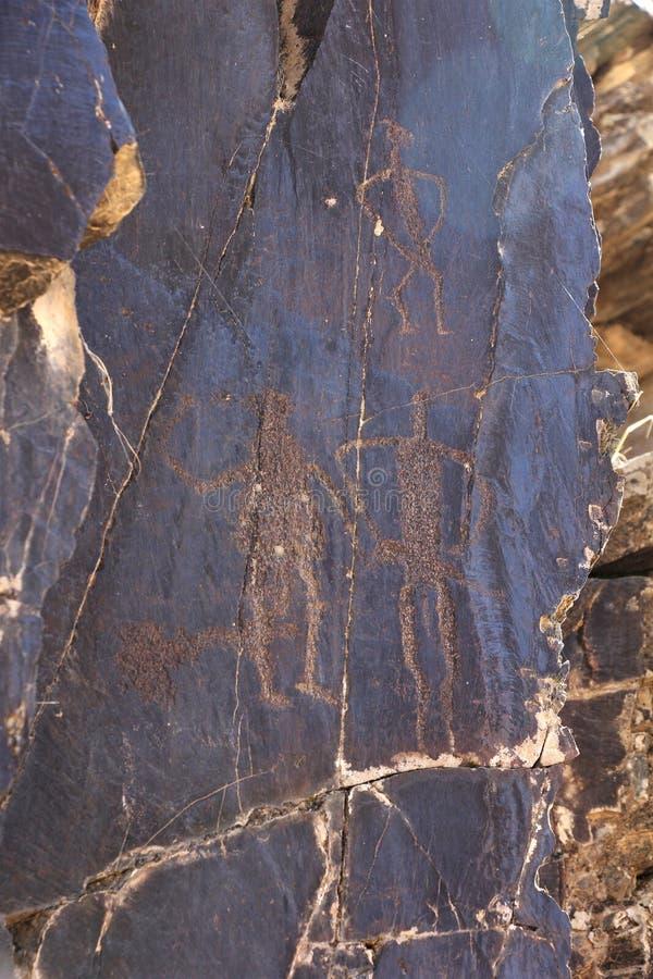 Petroglyph, mulher e homem dois antigos dos desenhos da rocha fotografia de stock royalty free