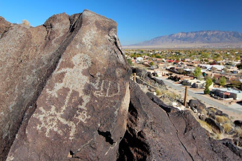 Petroglyphs, Petroglyph National Monument, Albuquerque, New Mexico. Petroglyphs and nearby housing development at Boca Negra, Petroglyph National Monument royalty free stock photos