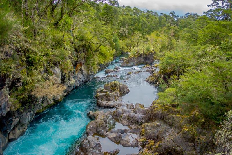 Petrohue flod som flödar till och med berget i Petrohue, Llanquihue landskap, region för Los Lagos, Chile royaltyfria bilder
