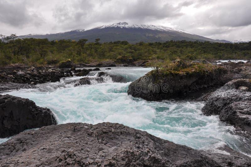 Petrohue härliga vattenfall med den Osorno vulkan bakom, Chile royaltyfri foto