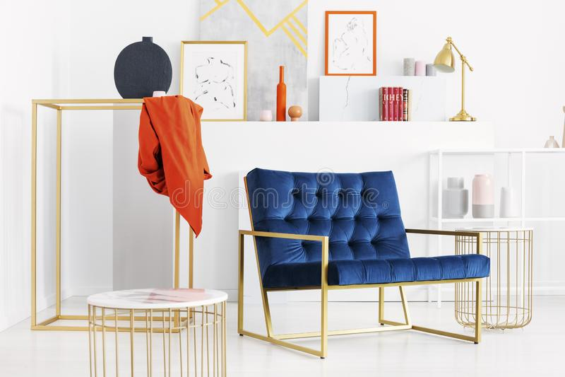 Petrol blue settee in the middle of stylish white living room with golden accessories and lot of art. Real photo stock photo