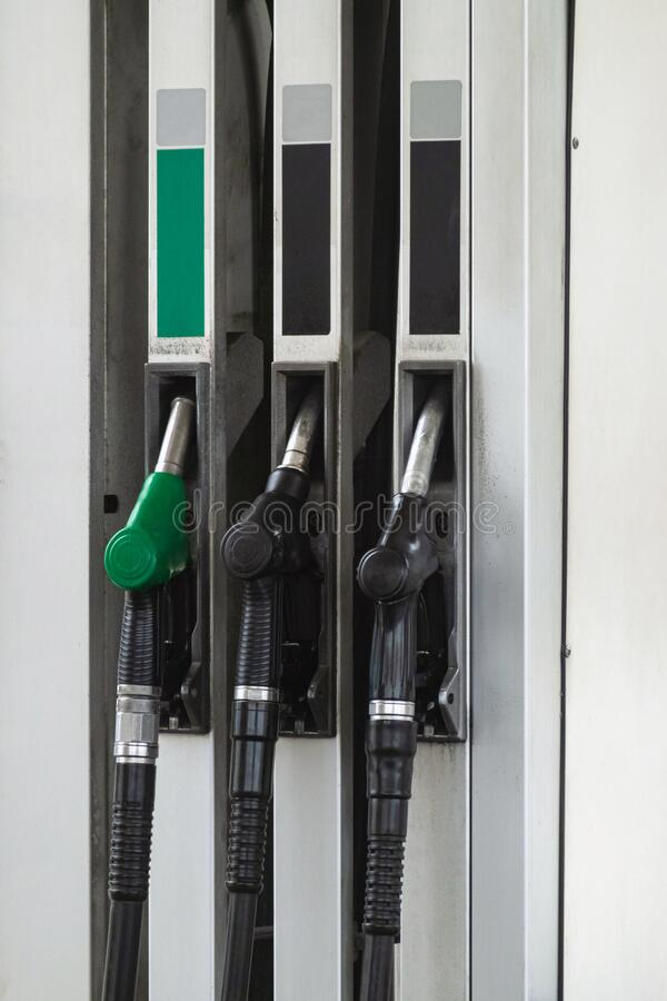 Petrol pump filling nozzles at gas station, nobody. Fuel pumps, self service.  stock photography