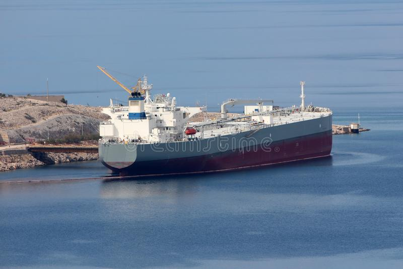 Petroleiro de óleo internacional estacionado no porto local que espera para ser descarregado cercado com escuro calmo - mar azul  foto de stock royalty free