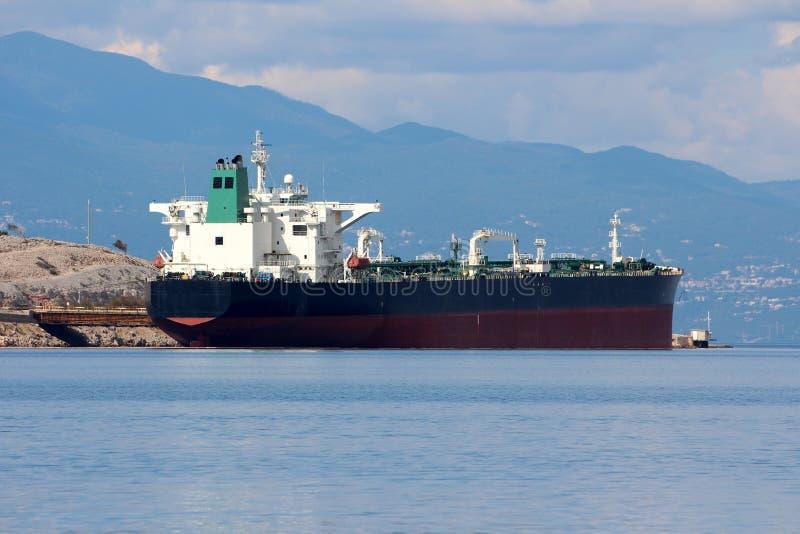 Petroleiro de óleo internacional que espera no porto local a ser descarregado cercado com o mar azul calmo e a costa de pedra com imagem de stock