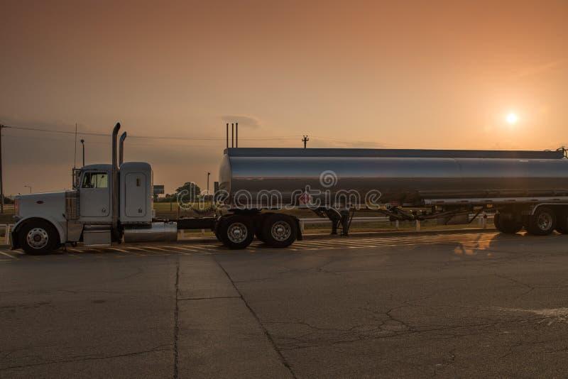Petroleiro grande do reboque de trator noun do caminhão do equipamento no alvorecer com o sol no fundo imagens de stock
