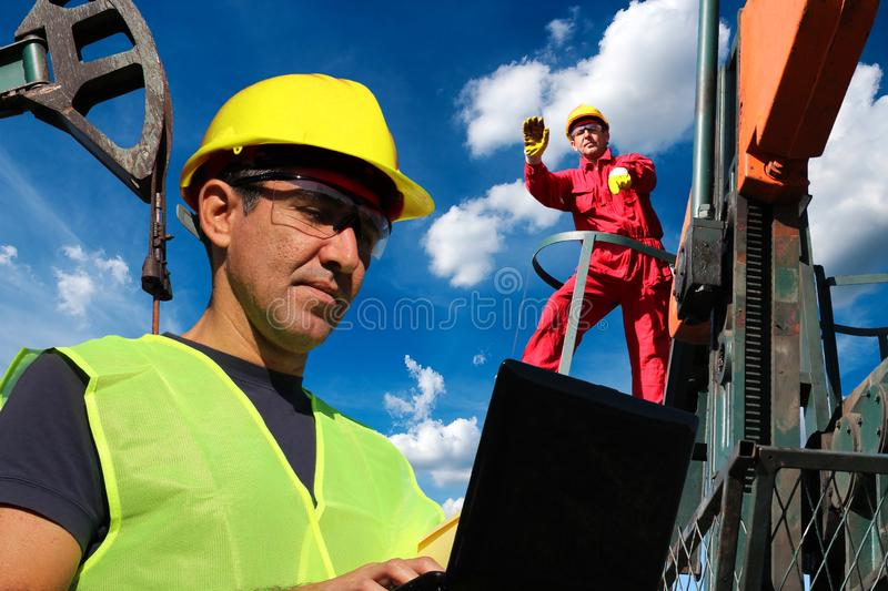 Petroleum Engineers Using Laptop And Oversee The Development Of An Oil Well. Petroleum engineers in the oilfield recording and updating information on oil stock photo