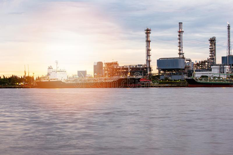 Petroleum oil refinery plant beside river in sunset. Time. Crude Oil Process machinery stock photo