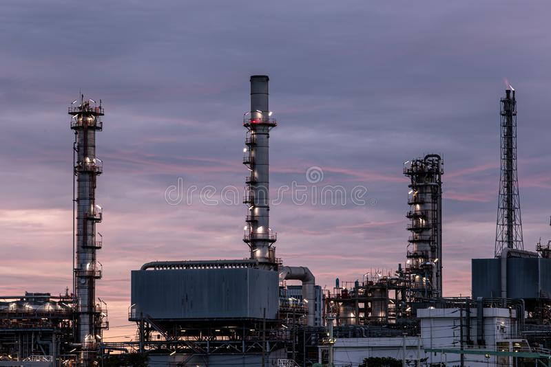 Petroleum oil refinery plant beside river in twilight time. Crude Oil Process machinery royalty free stock photography