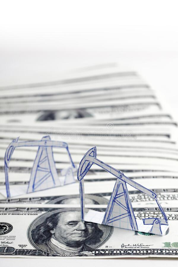 Petroleum pumpjack and oil rigs from paper on a heap of 100 dollar bills. Shallow focus. Concept image royalty free stock images