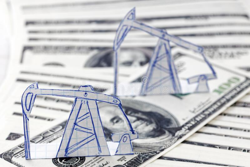 Petroleum pumpjack and oil rigs from paper on a heap of 100 dollar bills. Shallow focus. Concept image stock images