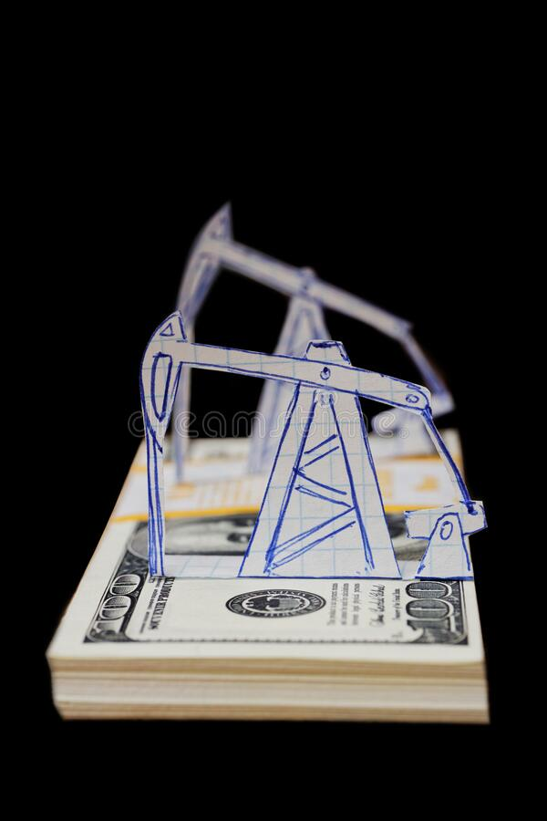 Petroleum pumpjack and oil rigs from paper on a pack of 100 dollar bills. Shallow focus. Isolated on black background royalty free stock photos