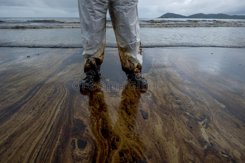 Petroleum spill mixed with other chemical substances on sea and sand surface. Pollution images, Samet Island, Thailand.  stock image