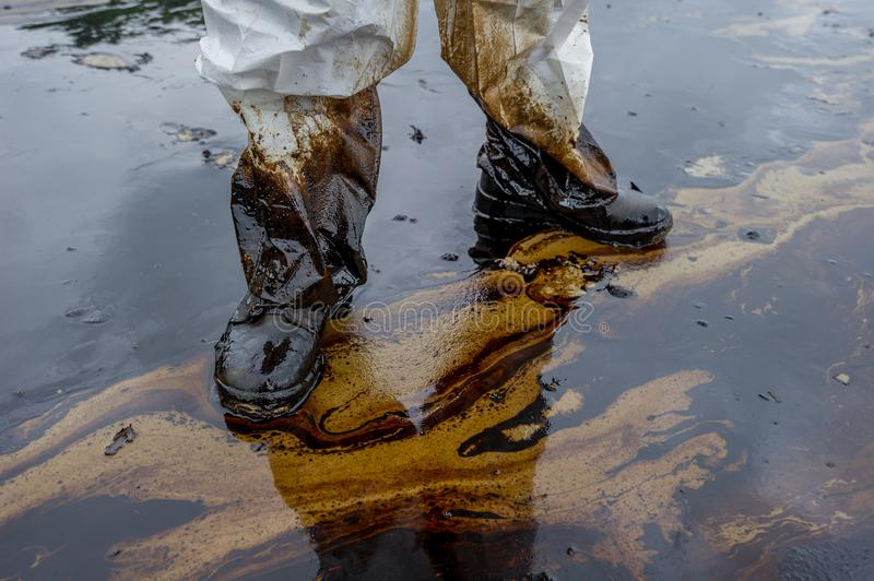 Petroleum spill mixed with other chemical substances on sea and sand surface. Pollution images, Samet Island, Thailand.  stock photography