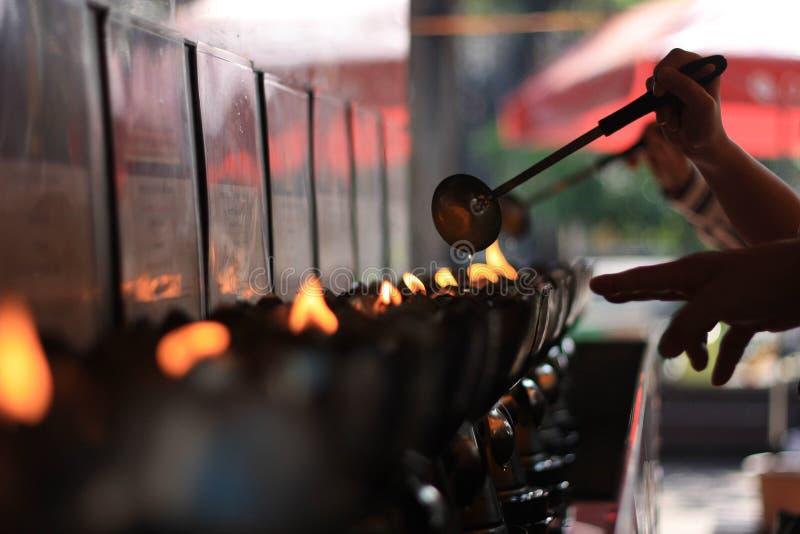 Petrolio ed acqua di versamento della candela di due genti buddisti sopra alle fiamme fotografia stock libera da diritti
