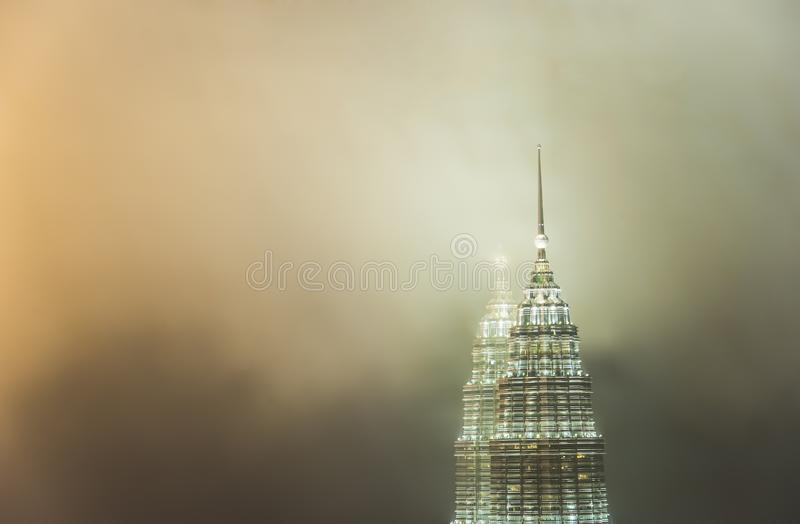 Petronas står hög (tvillingbrodern) i moln arkivfoton