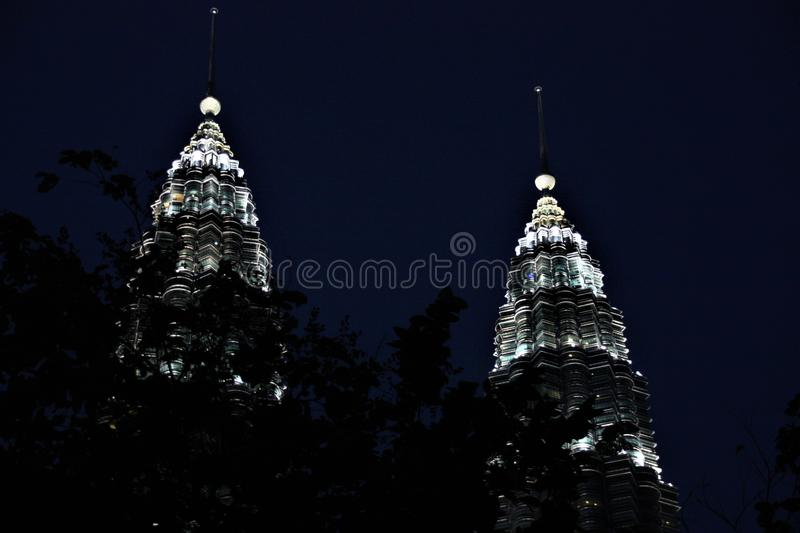 The Petronas Towers at night, tallest twin towers in the world at Kuala Lumpur Malaysia. The Petronas Towers, also known as the Petronas Twin Towers, are twin royalty free stock image