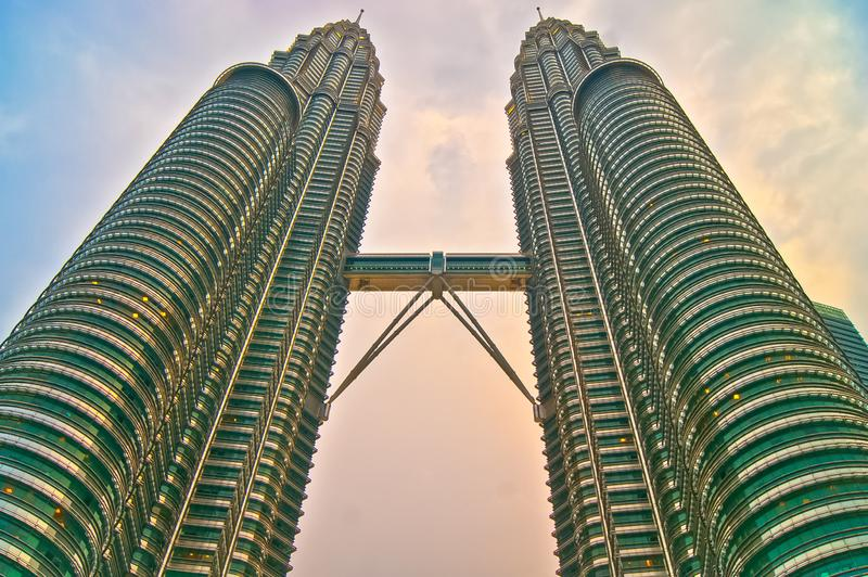 Petronas towers shot from below taken at sunset with the clouds on the background in kuala lumpur malaysia. Petronas towers shot at sunset with the clouds on the royalty free stock image