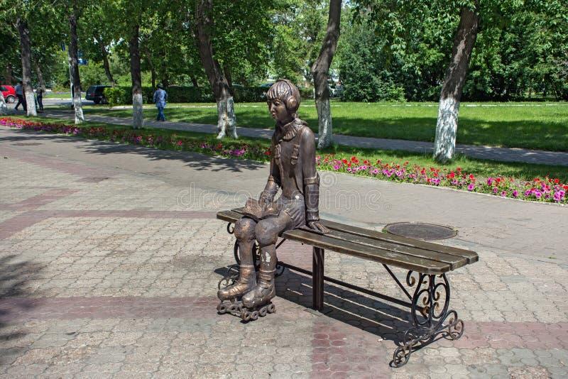 PETROPAVL, IL KAZAKISTAN - 24 LUGLIO 2015: Scultura della città di una ragazza sui pattini di rullo, che riposando su un banco fotografia stock