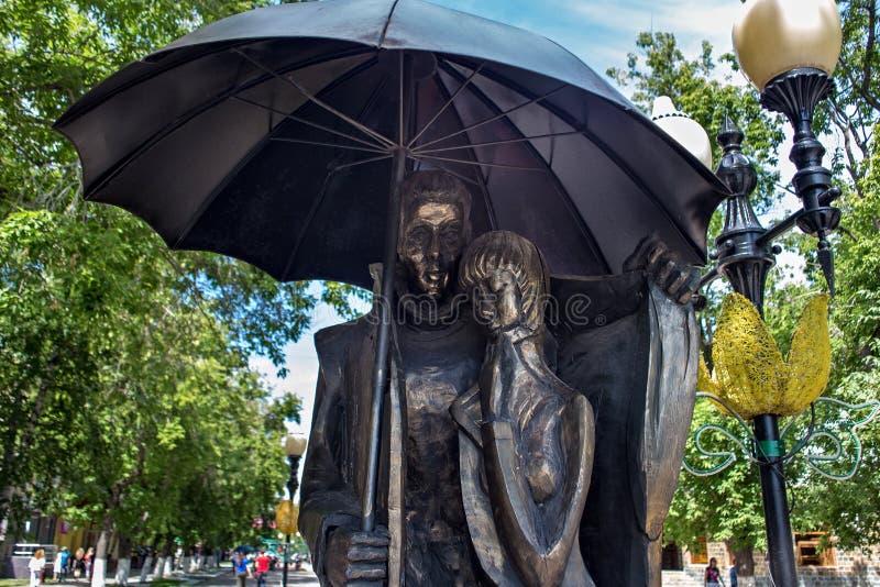 PETROPAVL, KASACHSTAN - 24. JULI 2015: Stadtskulptur eines Mannes und des jungen Mädchens unter einem Regenschirm auf einer Stadt stockfotos