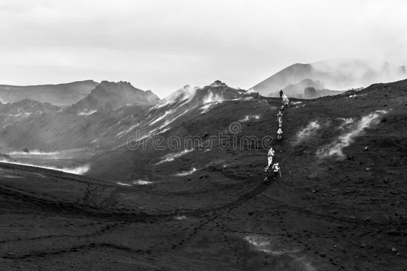 Petropavlovsk-Kamchatsky gebied, Rusland - Augustus 11, 2013: Groep toeristen die op een lavagebied dichtbij Tolbachik-Vulkaan lo royalty-vrije stock foto