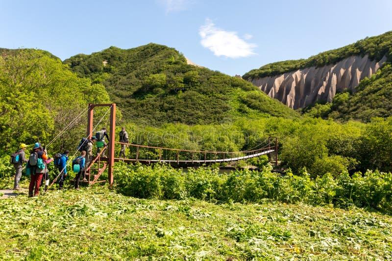 Petropavlovsk-Kamchatsky region, Ryssland - Juli 18, 2018: Grupp av turister som korsar floden på upphängningbron royaltyfria bilder
