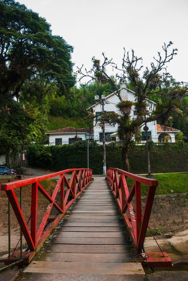 PETROPOLIS, RIO DE JANEIRO, BRASILE: Bella vecchia casa e un ponte di legno sopra lo stagno fotografia stock libera da diritti